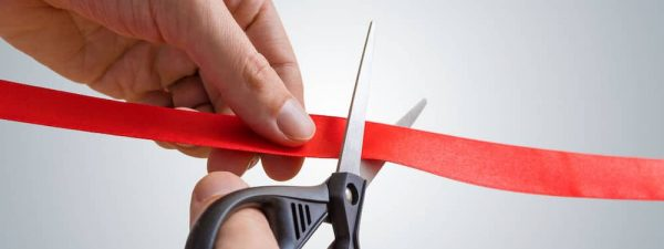 Man hands are cutting red ribbon with scissors. Opening event.